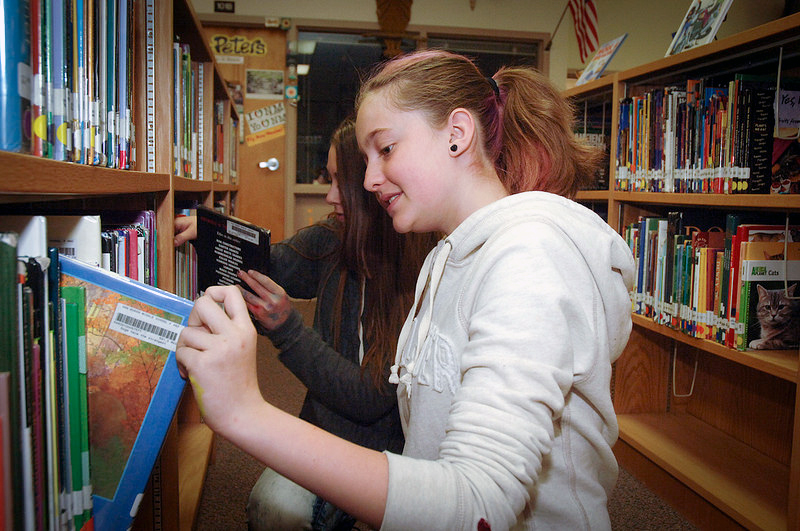 Students browse books on a shelf in a library